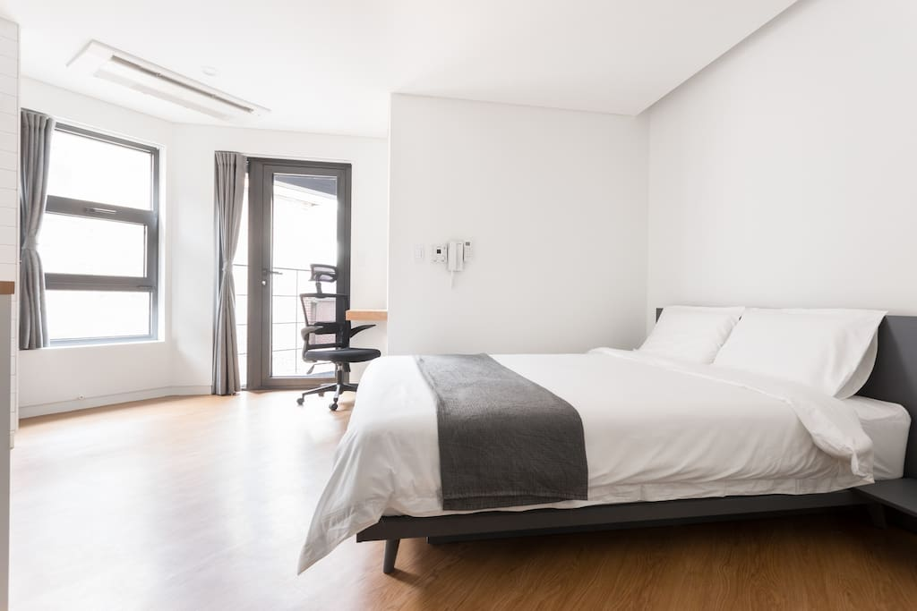 Each room features a comfy queen bed, work space, closet, balcony, and a bathroom.