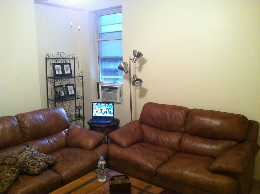 2 leather couches, 50+ inch TV on wall, one window