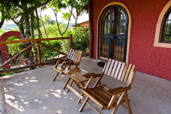 Relax in the private covered outdoor sitting area with views of the Pacific Ocean and shaded by a mango tree