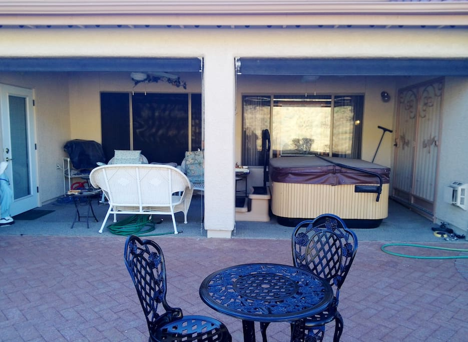 View of our private back patio with hot tub, seating area and a view of the wild hill behind our house