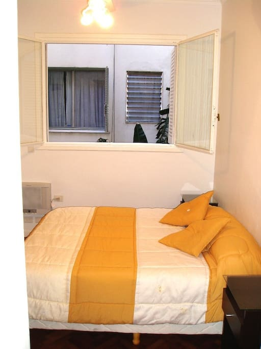 Bedroom with A/C, ceiling fan, queen bed, overlooking inner patio