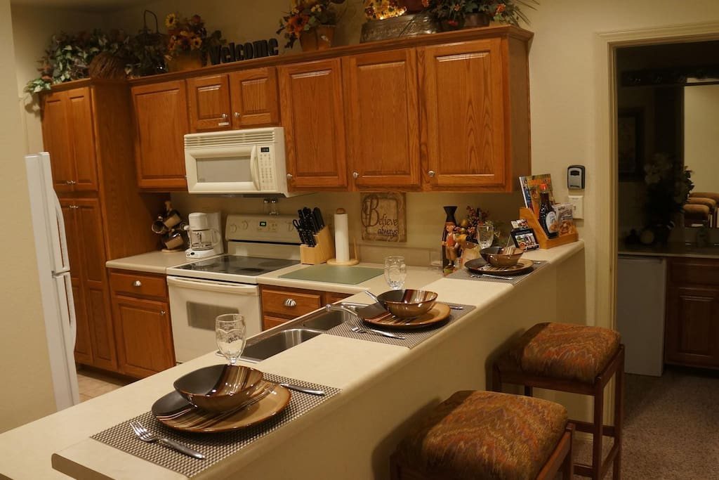 Kitchen has appliances and a bar that seats 4