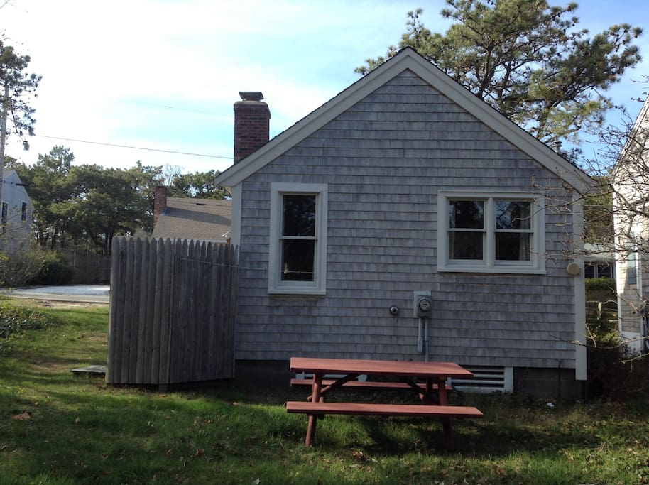 Back view of cottage with private picnic area and enclosed outside shower.