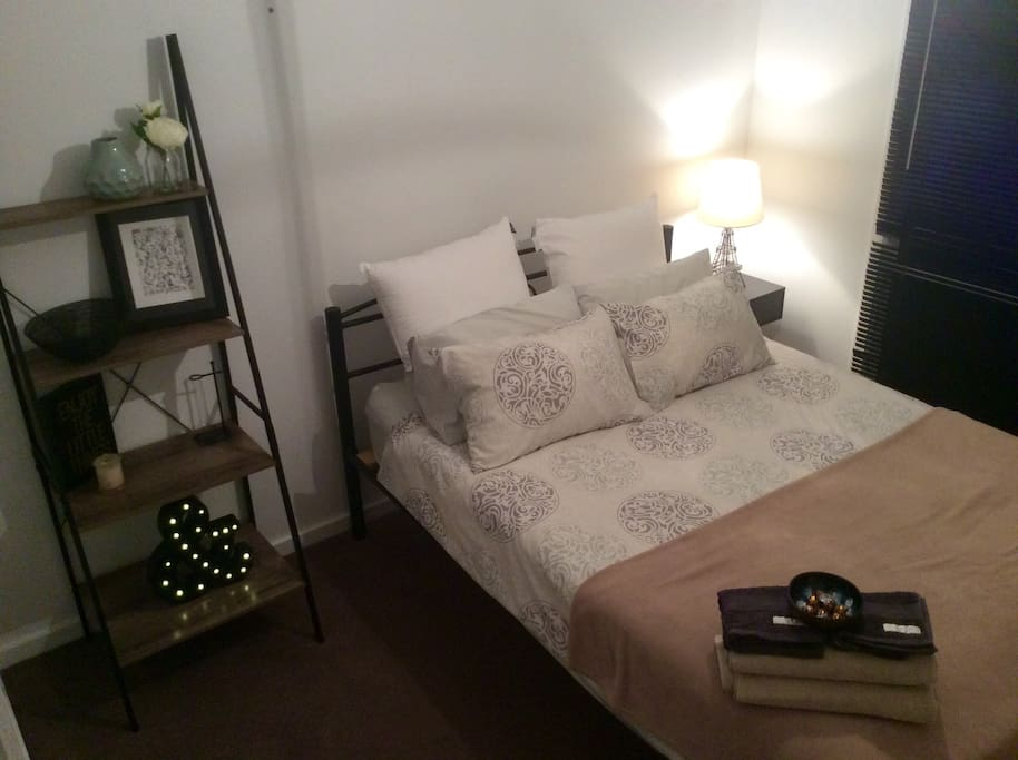 The bedroom with queen bed, bedside table and storage shelves.