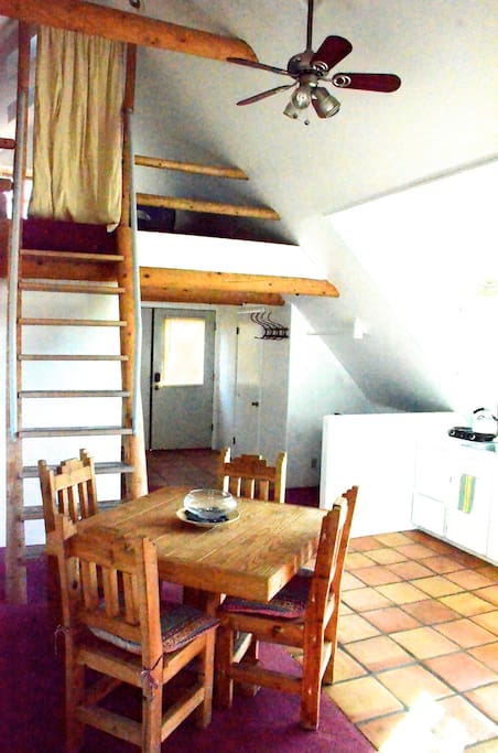View of the kitchenette, dining area, and entryway from the living room....upstairs is the loft, the Eagle's Nest.