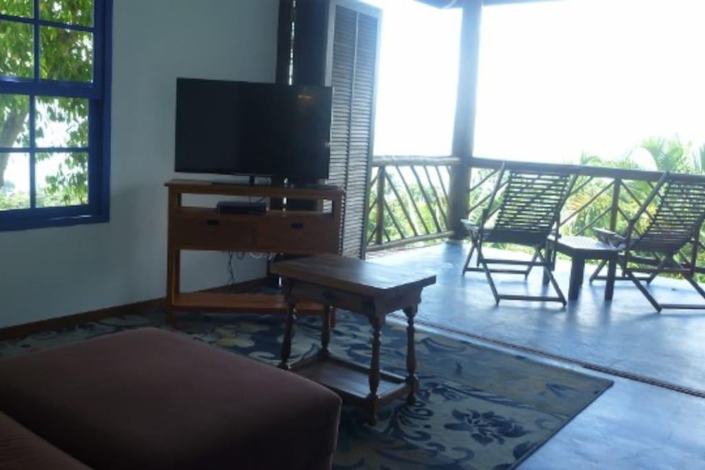 Sala com Pia, fogão, frigobar, Ventilador de teto,Sofá, TV e varanda com espreguiçadeiras e banco-mesa