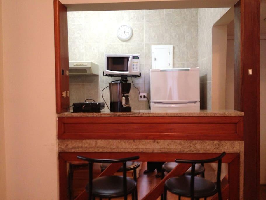 bancada que divide a cozinha da sala com bancos altos