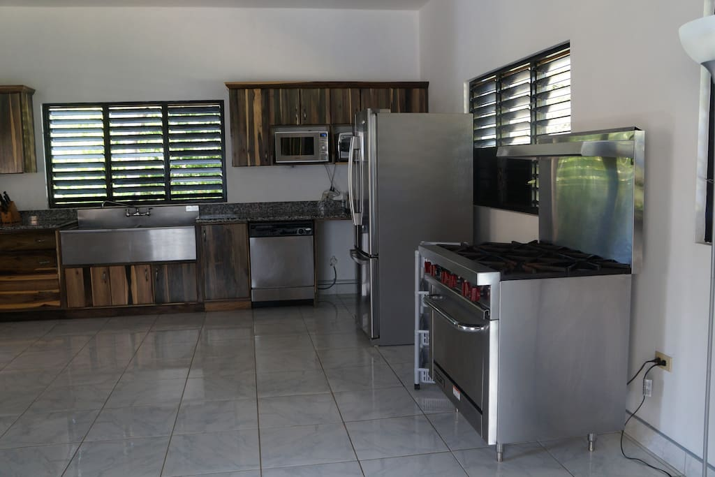 Large kitchen with granite counter tops and stainless  steel appliances.