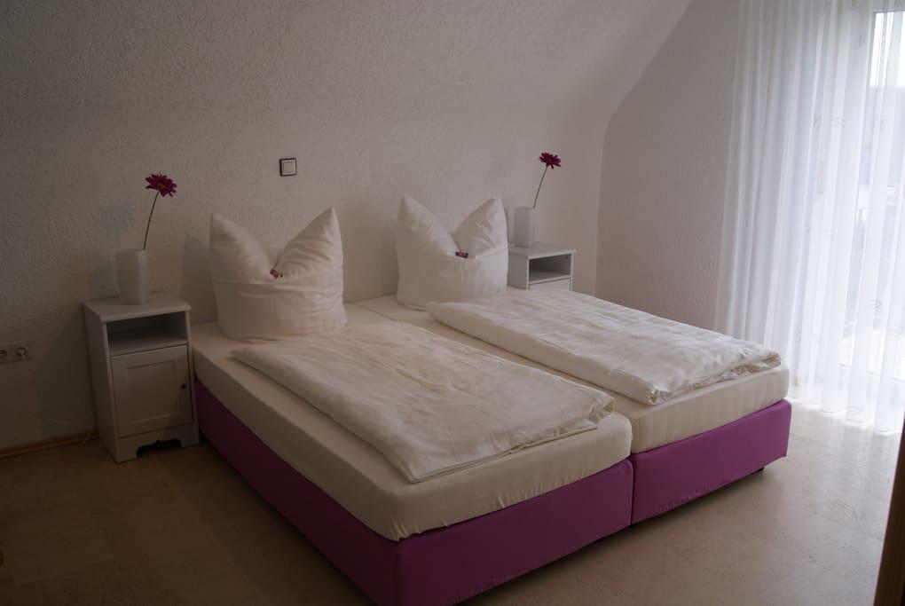 großes Schlafzimmer mit 3 Betten und Balkon