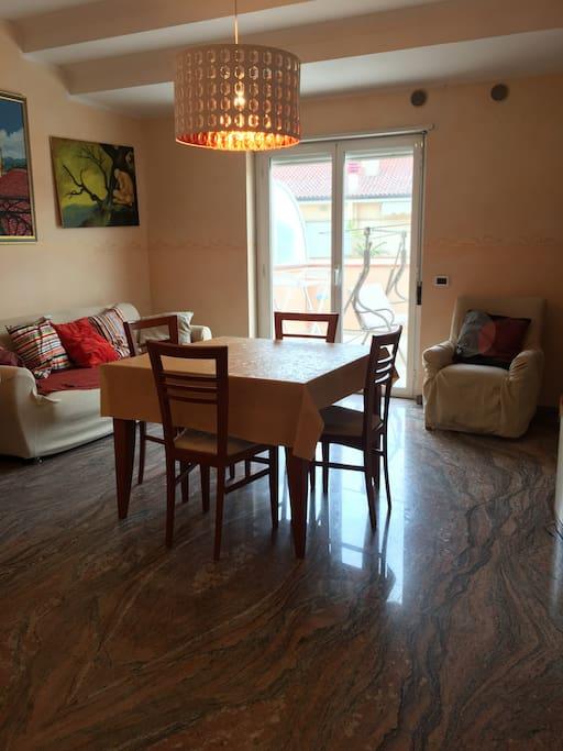 Soggiorno climatizzato, tavolo allungabile con 6 sedie, divano, poltrona e TV led. Portafinestra direttamente sul terrazzo