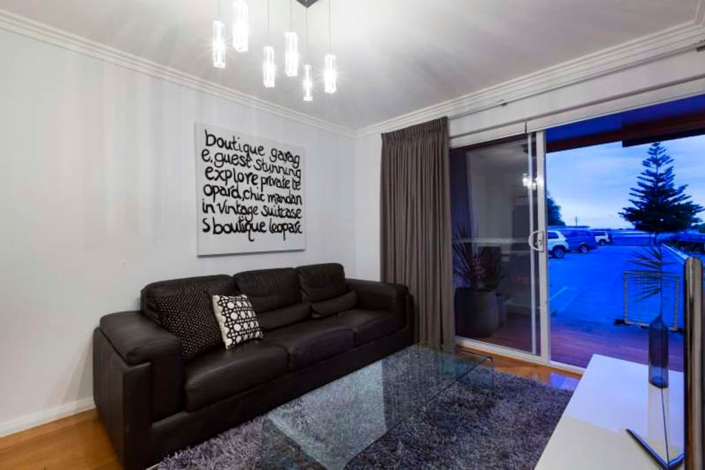 Lounge Room with double glazed doors.  Flat screen tv with leather couch
