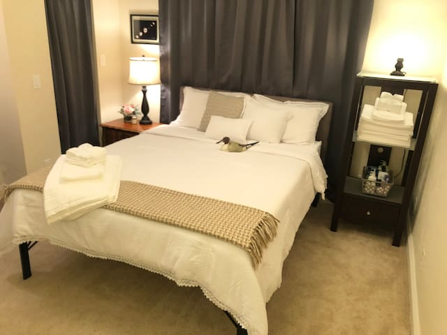 The room has a Queen bed with A shelf filled with extra towels and wash cloths.