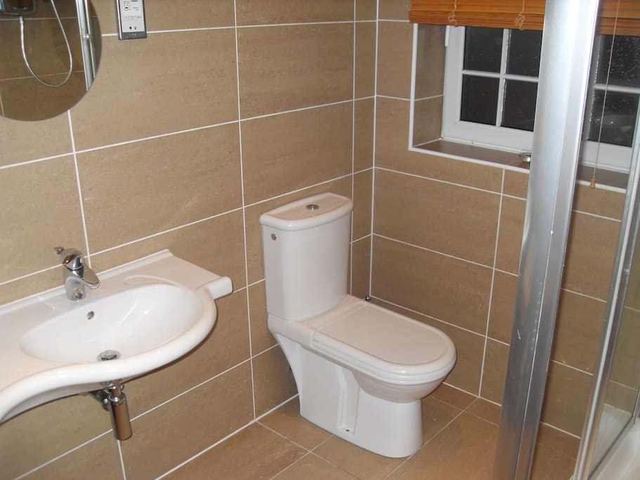 En-Suite with twin sinks, w/c and shower