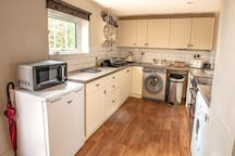 Fully equipped kitchen with full cooker, washing machine and tumble dryer.