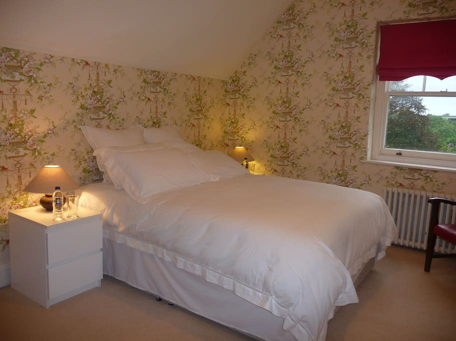 This gorgeous King size bedroom is tastefuly finished using 100% pure cotton quality white linen. It is peaceful and quiet with stunning views across the garden to fields and yet is only a 2 min flat walk to the centre of the village.