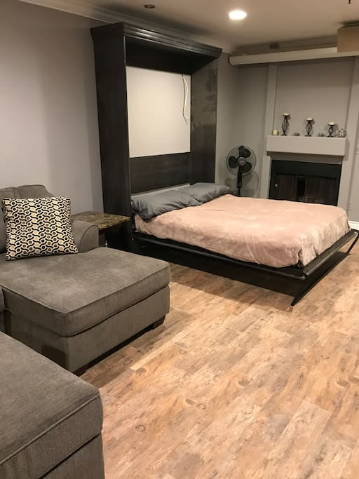 Spacious living room with Murphy bed shown open