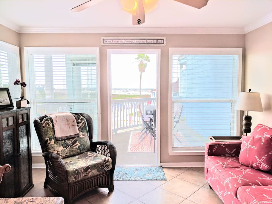 The living room has large windows, ocean views, and an oversized balcony with ample seating for outdoor drinks and dining.