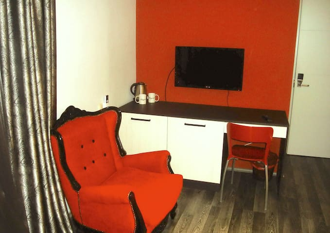 New flat screen TV, with comfortable table and space for a refrigerator, microwave and silverware.