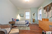 Full bed with quilt, kimono on the wall and two seats in this spacious room with historic floors.