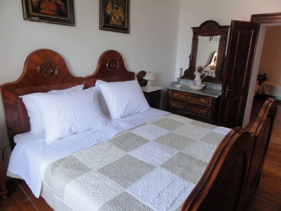Antique furniture and king sized bed in master bedroom.