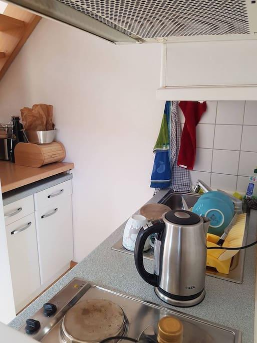 die kleine Küche mit zwei Herdplatten, einem Elektro-Ofen, einem Kühlschrank und einem Spühlbecken