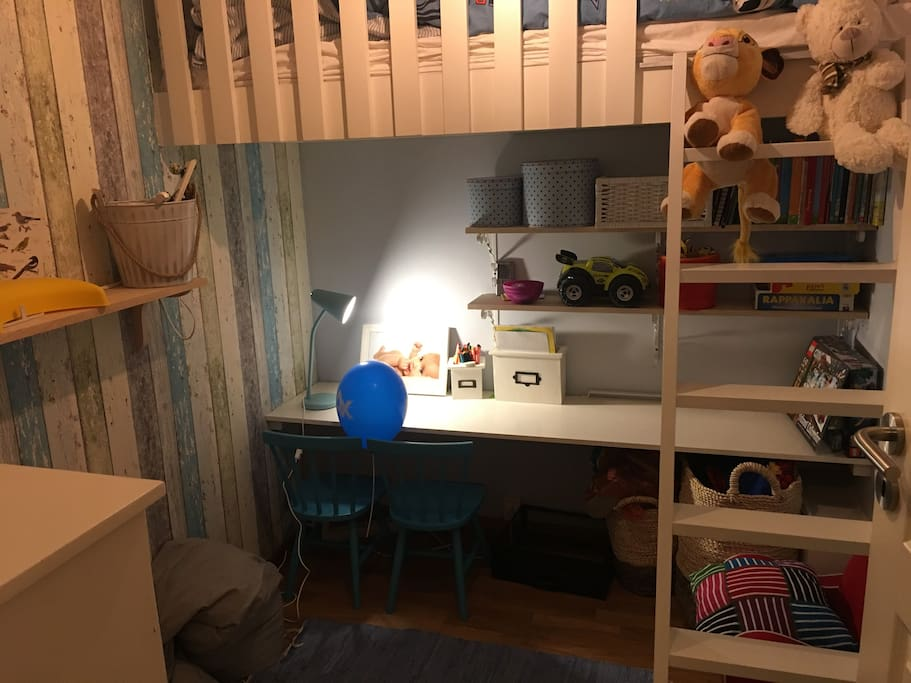 A small children's room with a loft bed (80*190cm), a desk underneath and toys