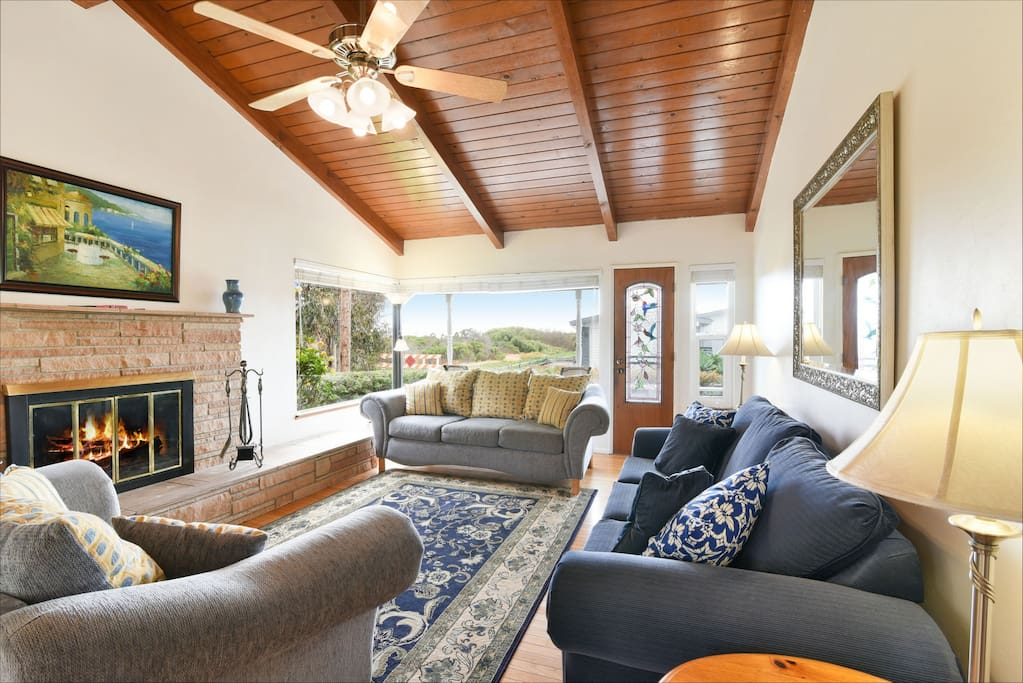 Enjoy peek ocean views, a fireplace and plenty of seating in this inviting living room that is adjacent to the kitchen and dining room.