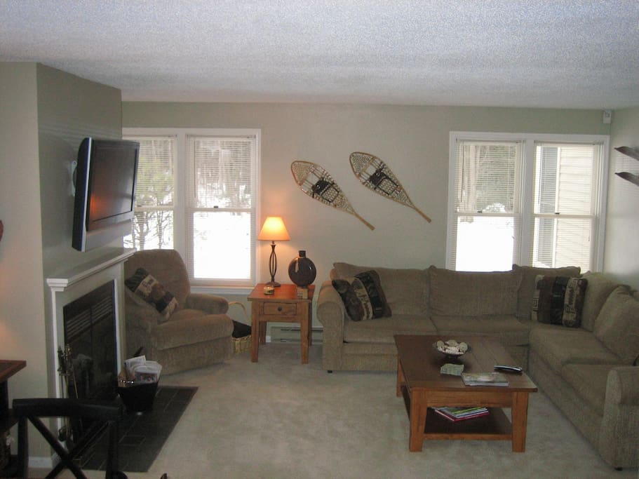 Family room with fireplace and mounted TV with cable.