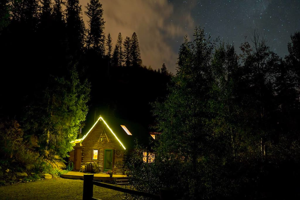 Cabin view at night with lush forest surrounding