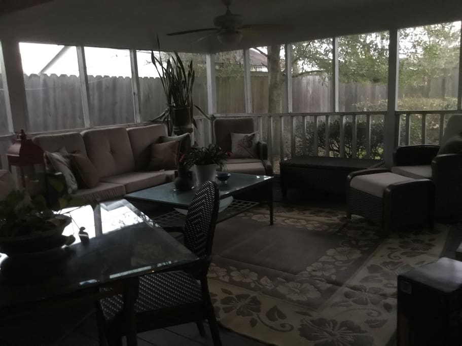 Large screened in porch with BBQ grill, eating and lounging areas, 32 inch tv