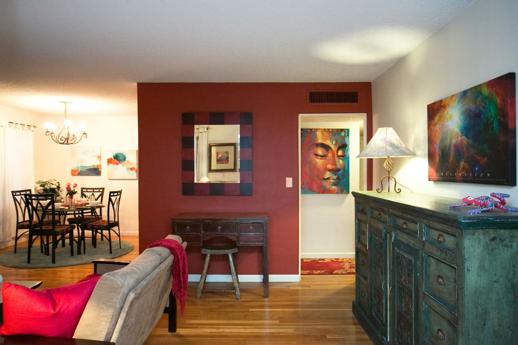Entrance way with side table storage, small desk and colorful artwork