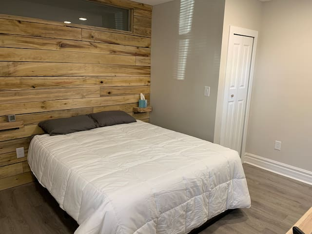 Queen bed on custom shiplap wall with glass insert