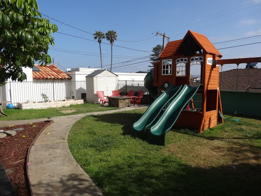 Backyard with play set and gas firepit