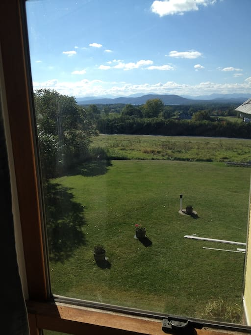 View from bedroom window. Lie in the new king size bed and view the mountains and a sliver of Lake Champlain.