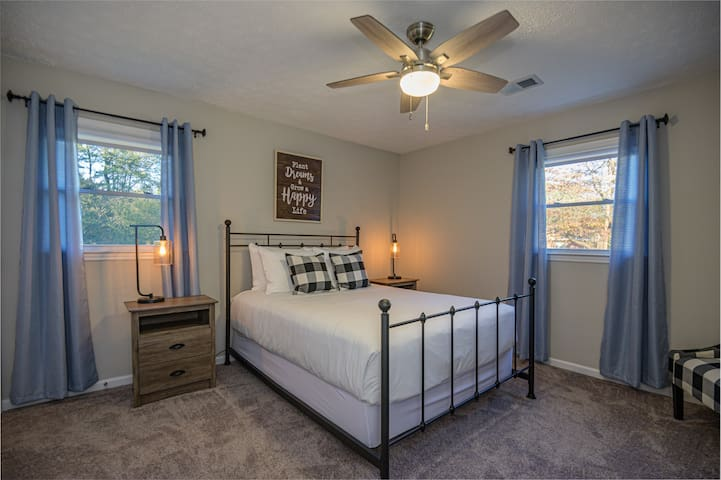 Guest bedroom has a queen size bed and ceiling fan.