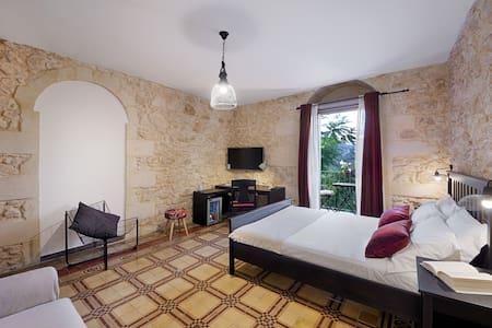 Camera matrimoniale con balcone vista collina e bagno privato.