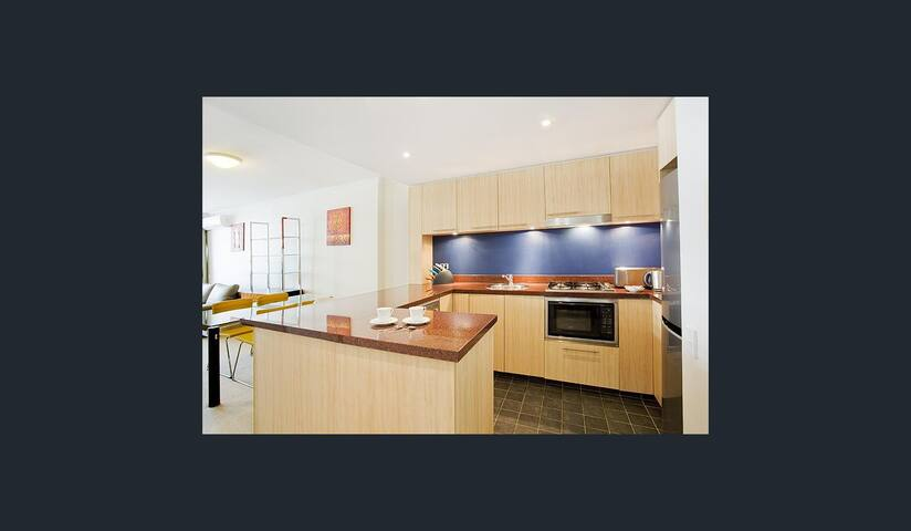 Dining space and open modern kitchen.  Dinning sets, glasses, etc are inside the cupboards. Vacuum cleaner, an oversize fridge/freezer, mini microwave, oven, toaster, kettle, washing machine, cloth dryer, dish washer, etc are included.