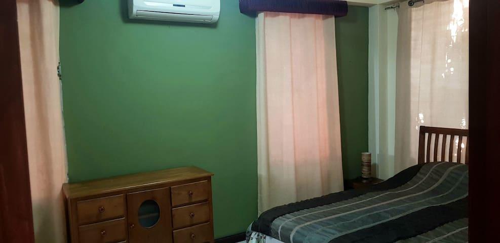 Une chambre climatisée avec un bon lit douillet, queen size, 2 tables et lampes de chevet