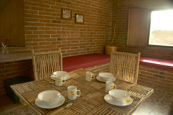 A comfortable dining table with kitchenware for four and the 2 futons behind for the 3rd and 4th guests.
