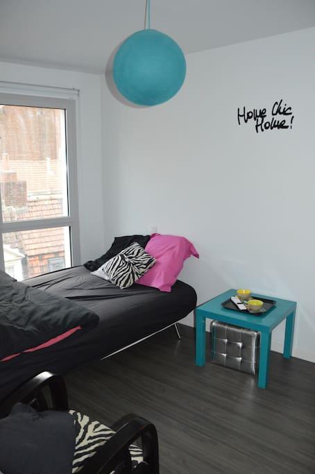Chambre Airbnb. Situé sur une rue très calme, elle dispose d une TV de deux fauteuils zèbre et d une petite table Ikea.