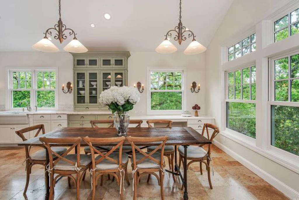 Custom built chef's eat-in kitchen, Wolf appliances, double sink-dishwasher configuration, expansive Carrara marble island, beverage fridge, and French doors leading to outdoor dining and spa area.