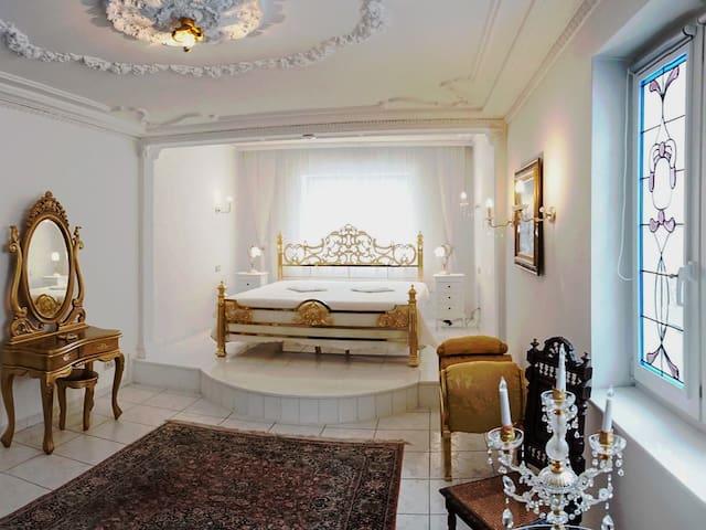 Schlafzimmer Nr. 1. Hartvergoldetes Doppelbett, 2m x 2m. Bleiverglastes Fenster. Überall viel Stuck