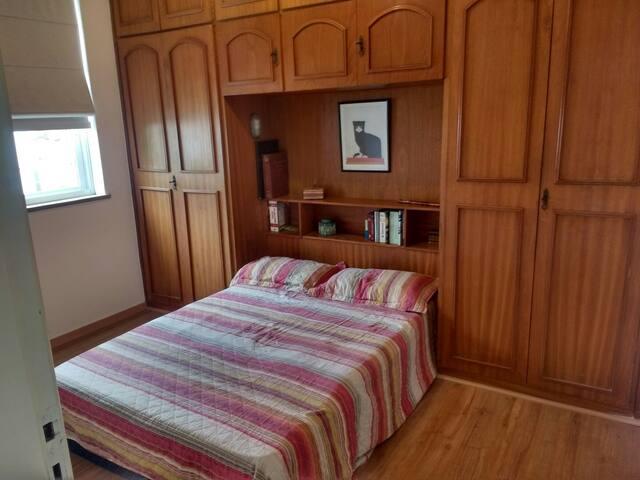Guest room with double bed and a spacious wardrobe.  Quarto com cama de casal e roupeiro espaçoso