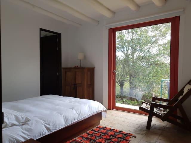 Alcoba principal en primer piso, vista al jardín, el bosque cercano y el valle al fondo. Baño fuera de la habitación.