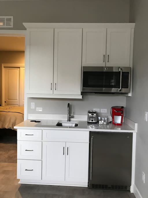Super cool kitchenette w/ fridge, microwave, Keurig & toaster that is stocked w/ dishes, items for cooking, etc.