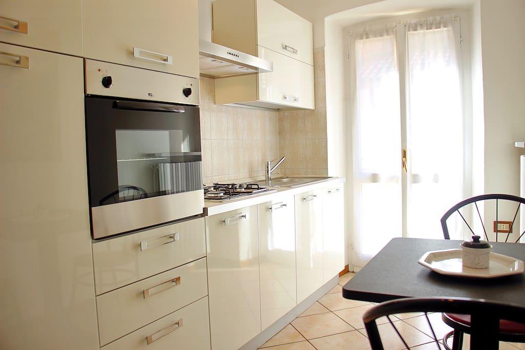 Cucina abitabile completa di tavolo, sedie per la prima colazione con forno elettrico e terrazzo.