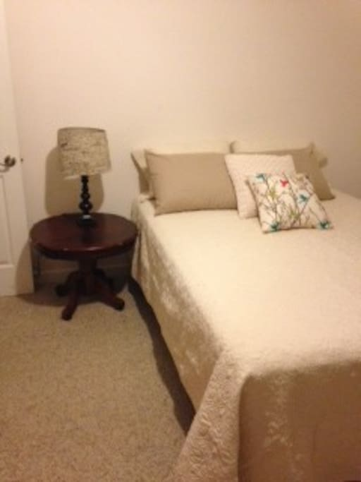 Queen bed with new bedding. Bathroom next to room.