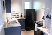 The kitchen has a full fridge, range and oven as well as granite countertops.