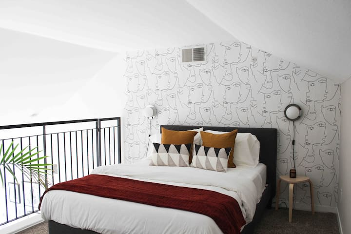 Loft-style guest bedroom with a queen size bed.