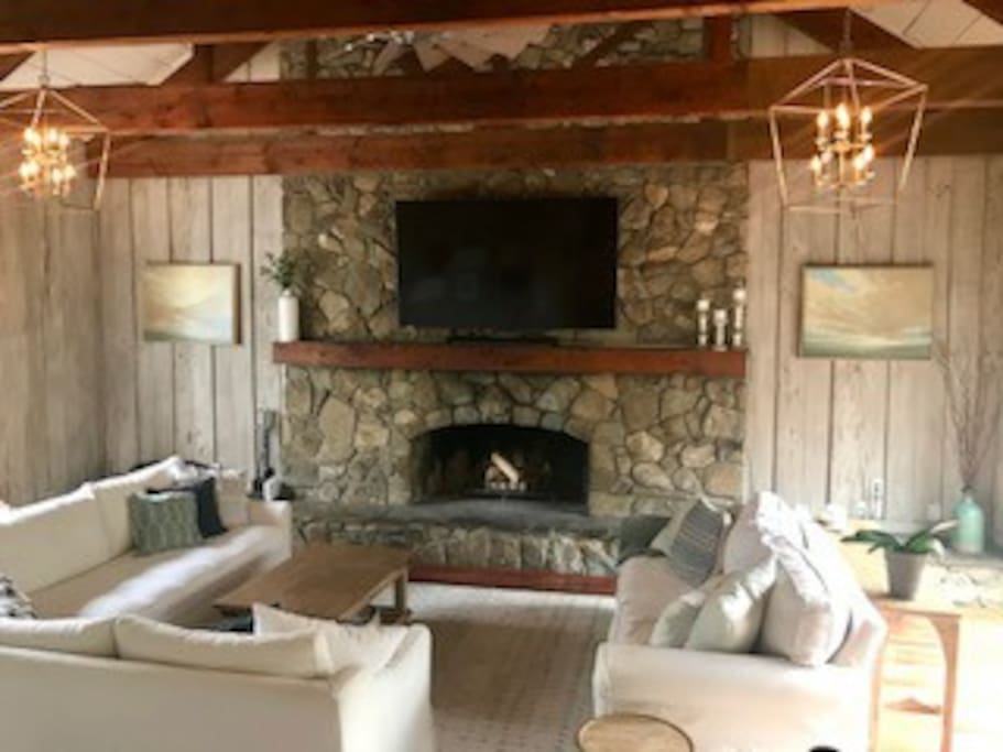 Family room with open beams, a huge stone fireplace, TV, and pull out couch for additional guests